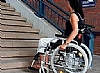 a person in a wheelchair infront of a staircase