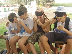 Four blindfolded children eat ice cream from a cup