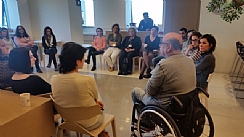 Participants listen to a guide in a wheelchair
