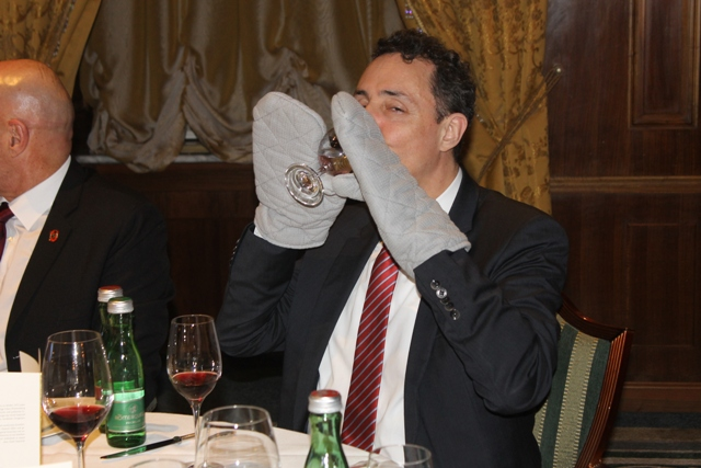 Participant at the Meal of the Senses drinks wine with stiff gloves on his hands